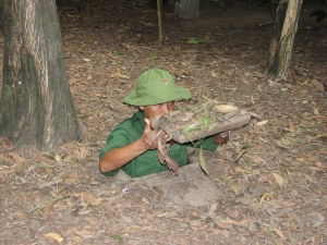 One of the Cu Chi Tunnels guide demonstrating how small an entry into the tunnel is.