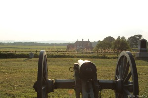 An artillery piece at Gettysburg National Military Park, with the Codori Farm in the distance.